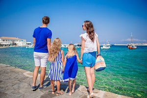 Family vacation in Europe. Parents and kids looking at old town Chora in Mykonos island, Greece