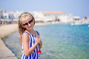 Adorable little girl at the most popular tourist area on Mykonos island, Greece. Beautiful kid smile and look in the camera on port background.