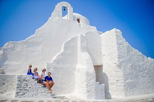Family vacation in Europe. Parents and kids sitting on the stairs of Paraportiani church on Mykonos Island, in Greece