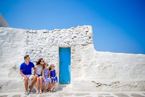 Family vacation in Europe. Parents and kids at street of typical greek traditional village with white walls and colorful doors on Mykonos Island, in Greece