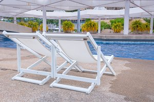 swimming pool with white deckchairs.