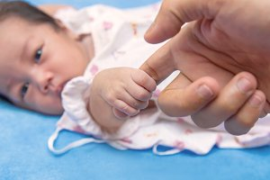 New born baby hand in mom palm