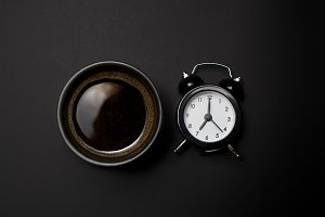 clock and coffee on black background