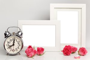 Blank frame, pink roses and clock