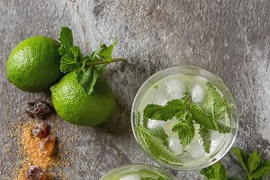 Glass tank mojito and Ingredients for cocktails. Fresh mint, limes, sugar over black backdrop. copy space. Top view