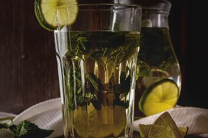 Mint iced tea with lime in the glass. Dark background.