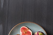 Juicy ripe figs on a plate. Dark wooden background. Top view