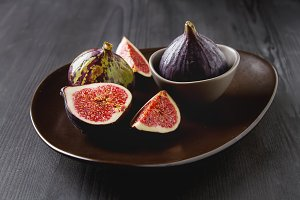 Juicy ripe figs on a plate. Dark wooden background