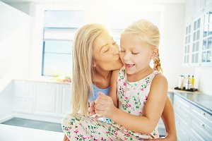 Mother kissing daughter in bright kitchen