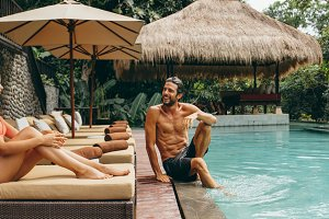 Couple relaxing at poolside