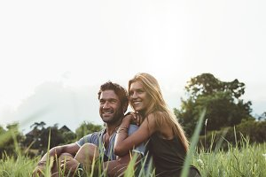 Loving couple sitting on grass field