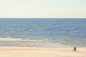 Cyclist rides along the beach sea