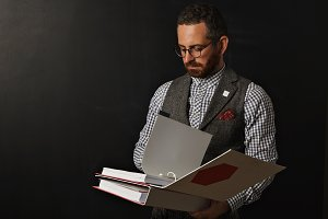 Stylish bearded teacher with binders at blackboard