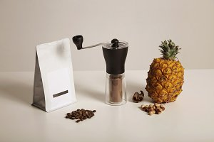 Coffee beans, grinder, pineapple, nuts and cinnamon