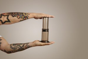 Closeup of tattooed man's hands holding aeropress