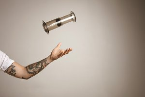 Tattoed man's arm throwing and catching aeropress