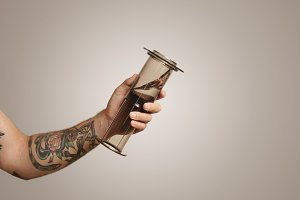 Closeup of tattooed man's hand holding aeropress