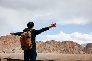 Happy young traveler spreading arms in city background in Leh, Ladakh, India