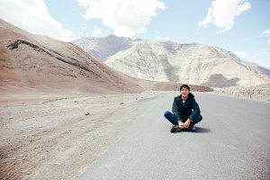 Young Asian male traveler sitting in the middle of empty road with freedom and joy in Leh, Ladakh, India