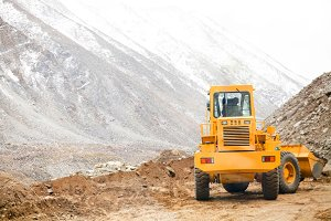 Big heavy machinery vehicle ploughing sand and stones to move path in snow mountain