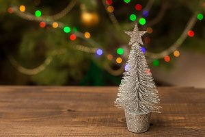 Decorated Christmas small silver tree on wooden table with glowing background