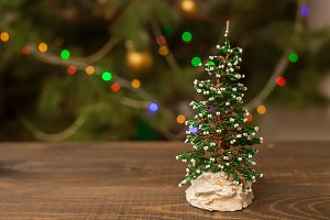 Decorated Christmas small tree on wooden table with glowing background