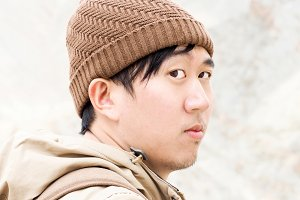 Close-up of Asian male traveler wearing beanie and rainy coat