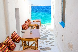 Benches with pillows in a typical greek bar in Mykonos with amazing sea view on Cyclades islands