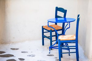 Two blue chairs on a street of typical greek traditional village on Mykonos Island, Greece, Europe