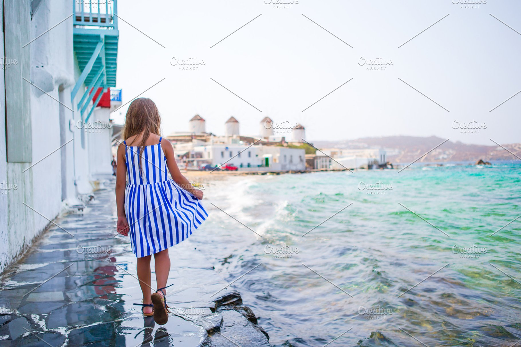 Adorable little girl at Little Venice the most popular tourist area on  Mykonos island, Greece  Beautiful kid smile and look in the camera on  Little