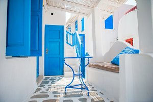 The narrow streets of the island with blue balconies, stairs and flowers. Beautiful terrace exterior with cycladic style.