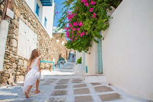 Adorable little girl in white dress having fun outdoors. Kid at street of typical greek traditional village with white walls and colorful doors on Mykonos Island, in Greece