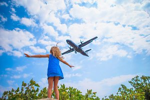 Adorable little child girl looking to the sky and flying plane directly above her. Beautiful exciting picture