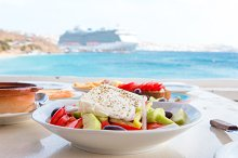 Delicious fresh greek salad served for lunch at outdoor restaurant with beautiful view on the sea and port