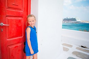 Cute girl in blue dress having fun outdoors near church. Kid at street of typical greek traditional village with white walls and colorful doors on Mykonos Island, in Greece