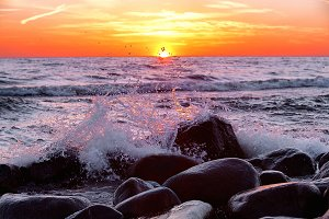 Splash of surf in the sea at sunset