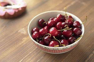 Cherries ripen a ceramic bowl