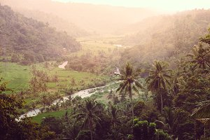 Beautiful soft sunrise light in tropical Bali village in high mountain jungle forest with calm river in Indonesia