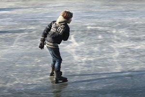 Boy skating on natural ice