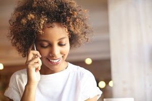 Fashionable good-looking black woman with cute smile and stylish hair, wearing white t-shirt and nose-ring, talking on phone with her friend, smiling, listening to latest news with cheerful expression