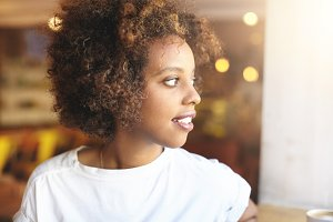 Profile of stylish good-looking young black woman with curly hair wearing casual top, looking through window at street, having rest at coffee shop, waiting for friend to join her for breakfast