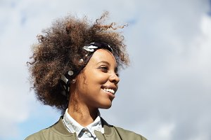 Attractive fashionable young African female with Afro haircut, looking into distance with happy dreamy smile, thinking about her life goals and future plans, standing against blue sky background