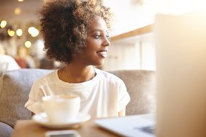 Young beautiful African female freelancer having cappuccino and using laptop computer for distant work, sitting on sofa at cafeteria, looking through window with cute smile, contemplating urban view