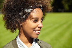 Profile of good-looking dark-skinned student girl with clean healthy skin and stylish hair, having nice walk along green lawn in city park in the morning, looking away with happy inspired smile