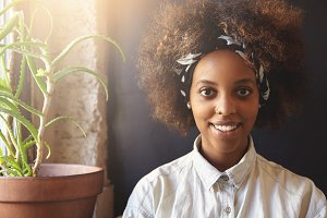 Fashionable dark-skinned hipster girl with Afro haircut wearing denim shirt and do-rag, looking and smiling at camera with happy expression. Cheerful black woman with facial piercing resting at home