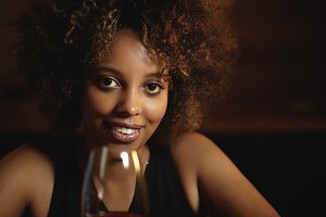 People and leisure. Attractive African female with mysterious smile and healthy shiny skin, holding glass of red wine, sitting against wooden wall background with copy space for your content