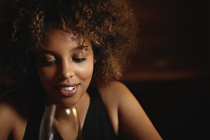 Portrait of dark-skinned girl with Afro hairstyle wearing black dress, relaxing at night club, smiling and looking down with flirting smile, enjoying red wine. Young African woman holding glass