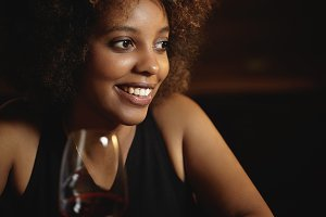 Headshot of beautiful stylish young African female with curlly hair siting at restaurant, holding glass of red wine, looking away with happy smile, spending evening with friends. Selective focus