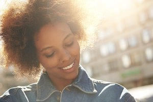 Attractive happy dark-skinned model with Afro hairstyle and nose-ring, posing outdoors against urban background during her morning walk, looking down with shy smile showing her white teeth. Flare sun