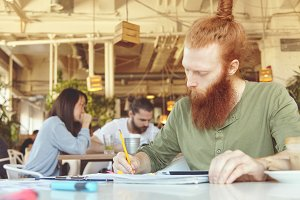 Portrait of young Caucasian journalist with long beard holding pencil, writing down in his notebook, making research while working on investigating report, sitting at coworking space, using touch pad